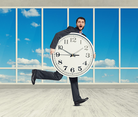 Running amazed man with big white clock in empty room with big running amazed man with big white clock in empty room with big windows stock photo thecheapjerseys Gallery