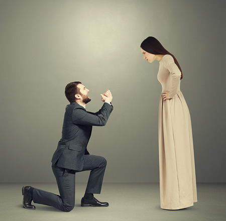 emotional couple: full length portrait of emotional couple over grey background. angry woman looking at man, man standing on knee and apologizing