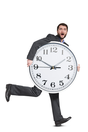 scared man holding big clock and running. isolated on white background photo