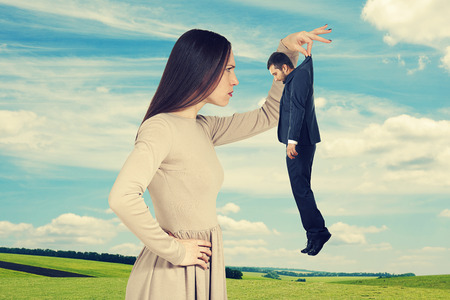 henpecked: serious young woman looking at small man over sky and green field