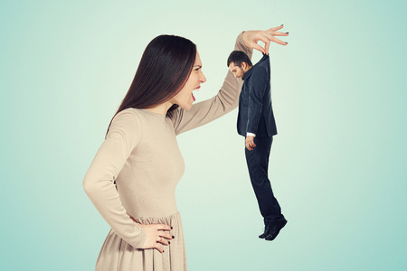 henpecked: aggressive young woman holding small man and screaming at him. photo over blue background