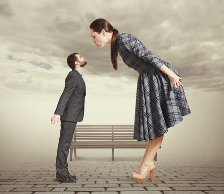 big and small: attractive young woman bending forward and kissing small man. photo in park