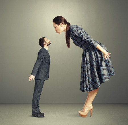 bending over: beautiful woman bending forward and kissing small man over dark background Stock Photo