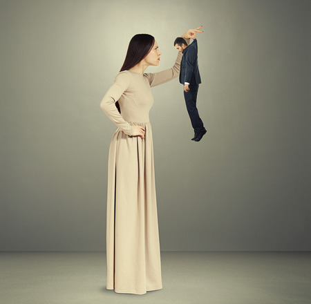 scold: beautiful young woman scrutinizing small man in black suit over grey background Stock Photo