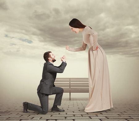 emotional couple: full length portrait of emotional couple in foggy park. woman screaming and showing fist, man standing on knee and apologizing
