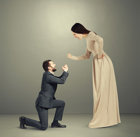 supplicate: full length portrait of emotional couple over grey background. woman screaming and showing fist, man standing on knee and apologizing