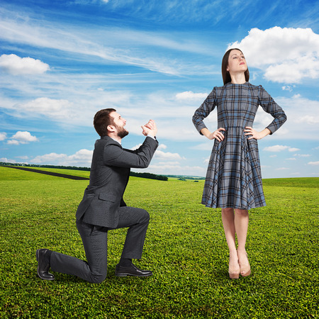supplicate: crying man looking at beautiful woman and asking for forgiveness. photo at outdoor Stock Photo