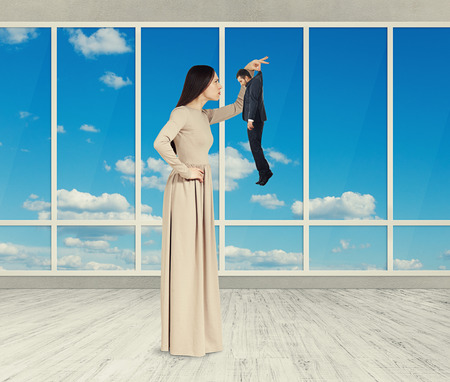 henpecked: serious pretty woman looking at sad small man. photo in empty room with big windows Stock Photo