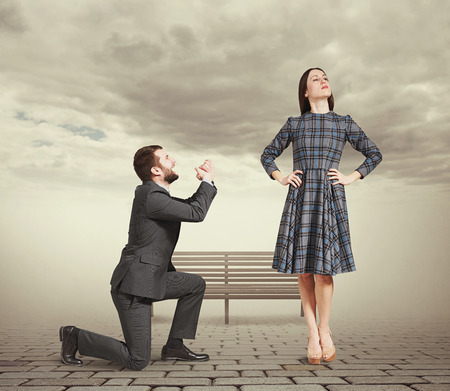 supplicate: sad man kneeling on one knee, looking at young attractive woman and asking for forgiveness. photo at outdoor Stock Photo