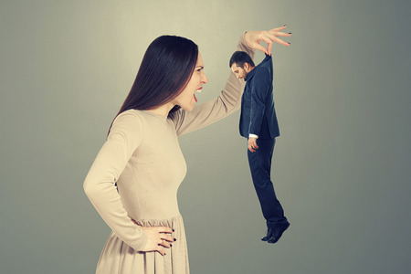 henpecked: emotional screaming woman looking at small young man over dark background Stock Photo