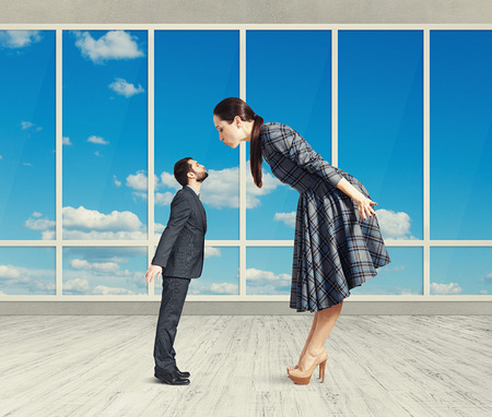 big woman bending forward and kissing small man. photo in room with big windows Stock Photo