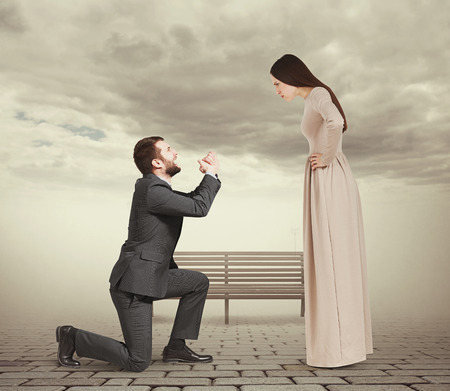 supplicate: beautiful woman looking at man standing on knee and apologizing. photo in foggy park Stock Photo