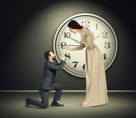 supplicate: angry yelling woman and crying man in dark room with big clock on the wall