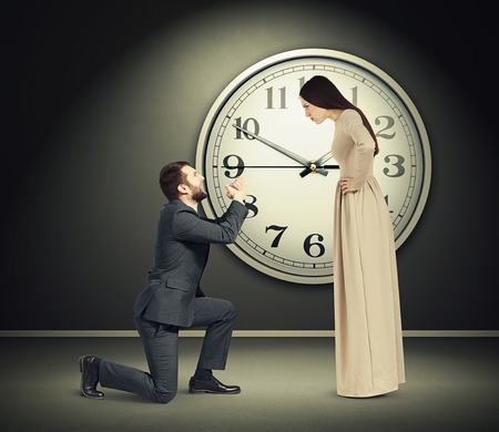 supplicate: angry young woman staring at latecomer crying man on one knee. concept photo in dark empty room with big white clock on the wall