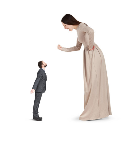 discontented: angry yelling woman waving fist and looking at small kissing man. isolated on white background Stock Photo