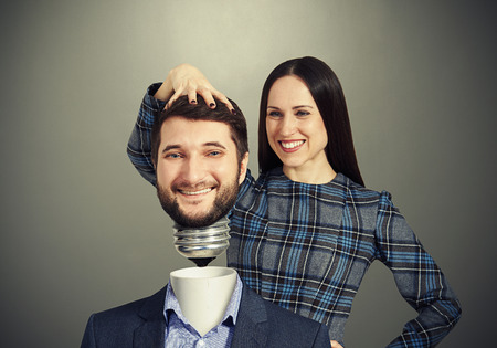 smiley woman fixing man over dark background photo