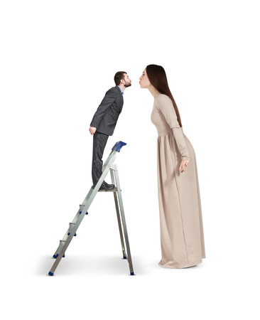 beautiful young woman raising forward and kissing small man on stepladder. isolated on white background Stock Photo