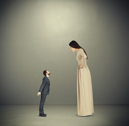 discontented woman staring at small kissing man. photo over dark background