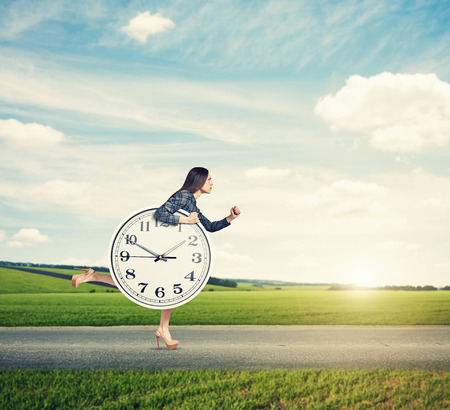 woman holding big clock and running forward on the road at outdoor