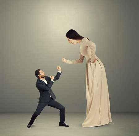henpecked: angry yelling woman showing fist to small scared man. photo over dark background