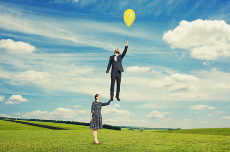 flying man: young beautiful woman holding flying man. photo at outdoor Stock Photo