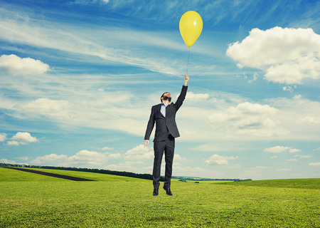 merriment: laughing man flying with yellow balloon at outdoor