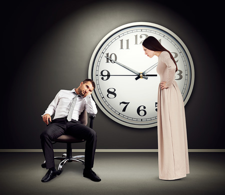 lazybones: angry woman staring at lazy man on chair. photo in empty dark room with big white clock on the wall Stock Photo