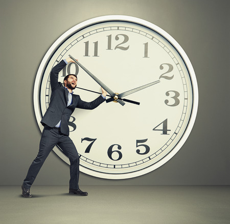 emotional businessman picks up the clock photo