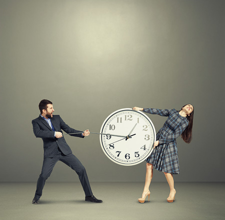 emotional couple: emotional couple stretching out the clock and screaming over dark background Stock Photo