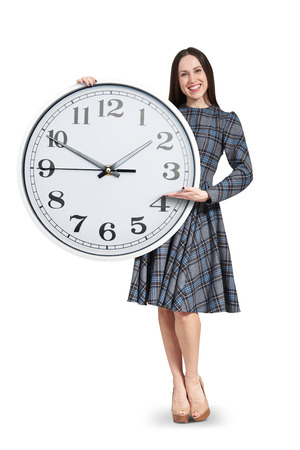 smiley beautiful woman holding big white clock and pointing at the time. isolated on white background photo