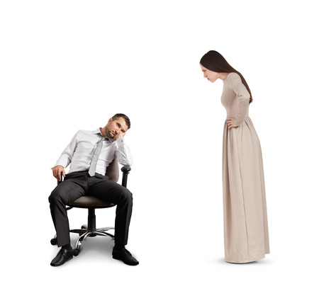 lazybones: strict woman looking at tired man in chair. isolated on white background