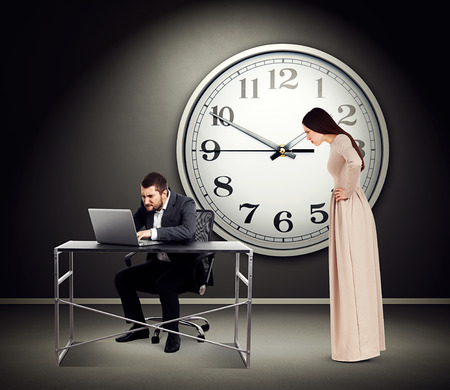 workaholic: young beautiful woman staring at man with laptop. photo in dark room with big white clock on the wall Stock Photo