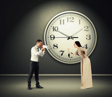 angry yelling woman and screaming man with megaphone in dark room with big clock on the wall photo
