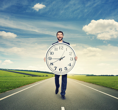 laughing man walking on the road and holding big white clock photo