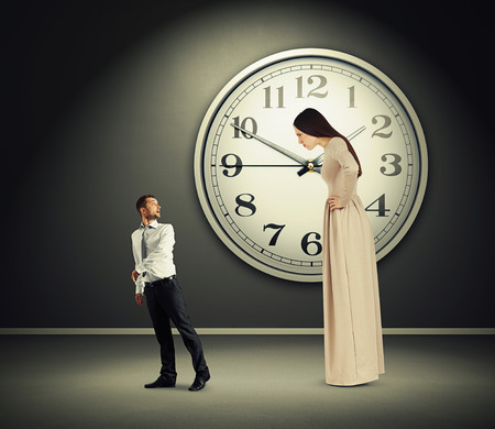 discontented: small man going away and turning round. big discontented woman looking at man. photo in dark room with big white clock on the wall