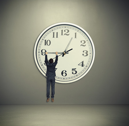 businessman hanging on big clock hand. big clock on grey wall photo
