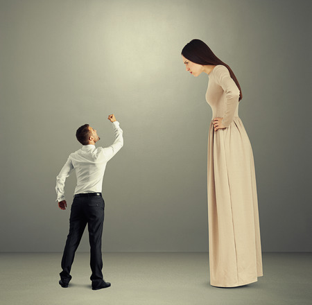 henpecked: small angry man showing fist to dissatisfied woman in long dress over grey background