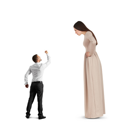 henpecked: angry small man waving his fist, screaming and looking at big serious woman in long dress. isolated on white background