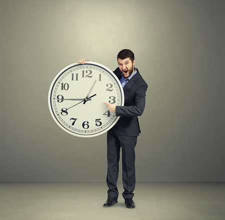 emotional businessman holding big white clock, pointing, screaming and looking at camera against dark background photo