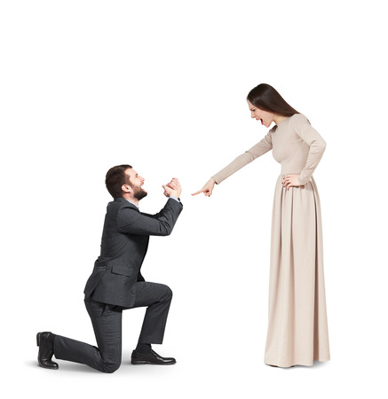 supplicate: full length portrait of emotional couple over grey background. angry woman pointing and screaming at man, man standing on knee and apologizing. isolated on white background Stock Photo