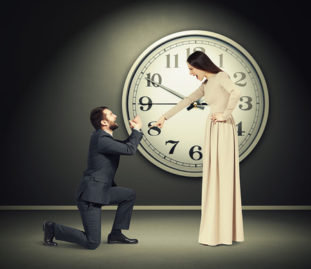 supplicate: angry yelling woman pointing finger at crying man in dark room with big clock on the wall