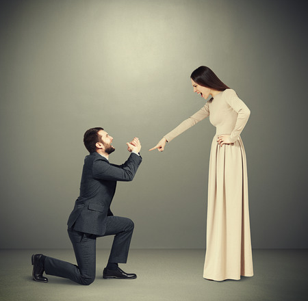 supplicate: full length portrait of emotional couple over grey background. angry woman pointing and screaming at man, man standing on knee and apologizing