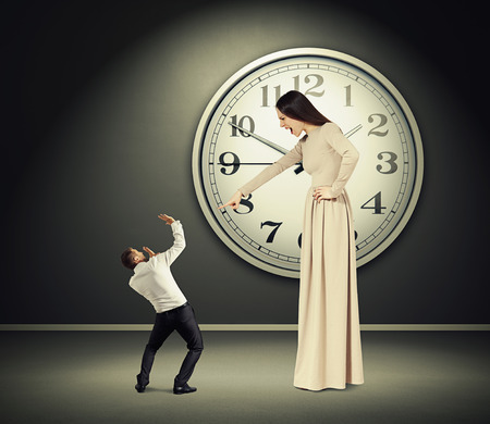 squabble: angry yelling woman pointing at scared man with in dark room with big clock on the wall