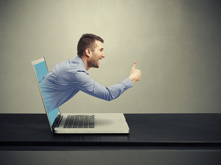 social emotional: laughing man got out of the laptop and showing thumbs up against dark background