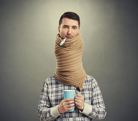 sick person: sad man with long neck coiled scarf over dark background Stock Photo