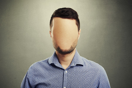 anonymous man with blank face against dark background