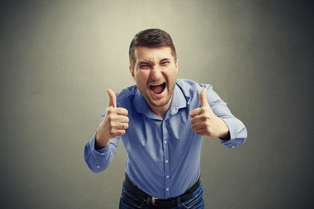 two thumbs up: happy man showing two thumbs up and laughing over dark background Stock Photo