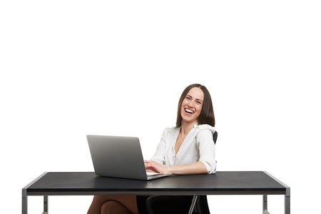 alluring women: laughing young woman working with laptop and looking at camera. isolated on white background