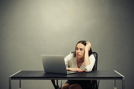 vermoeide zakenvrouw kijken naar de monitor en verdrietig over donkere achtergrond gevoel