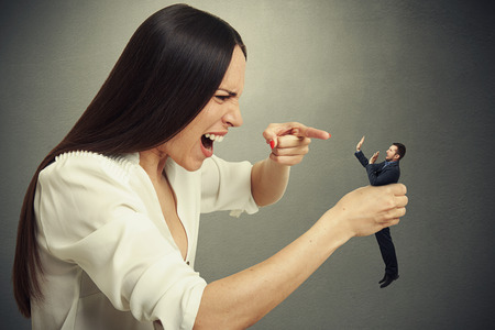 emotional woman holding in hand small scared man, pointing at him and yelling. photo over dark background Stock Photo